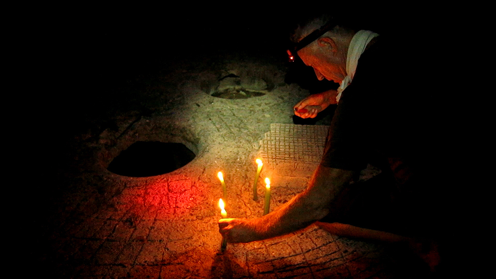 Neil lighting candles beside the hole in the cistern in the prison yard